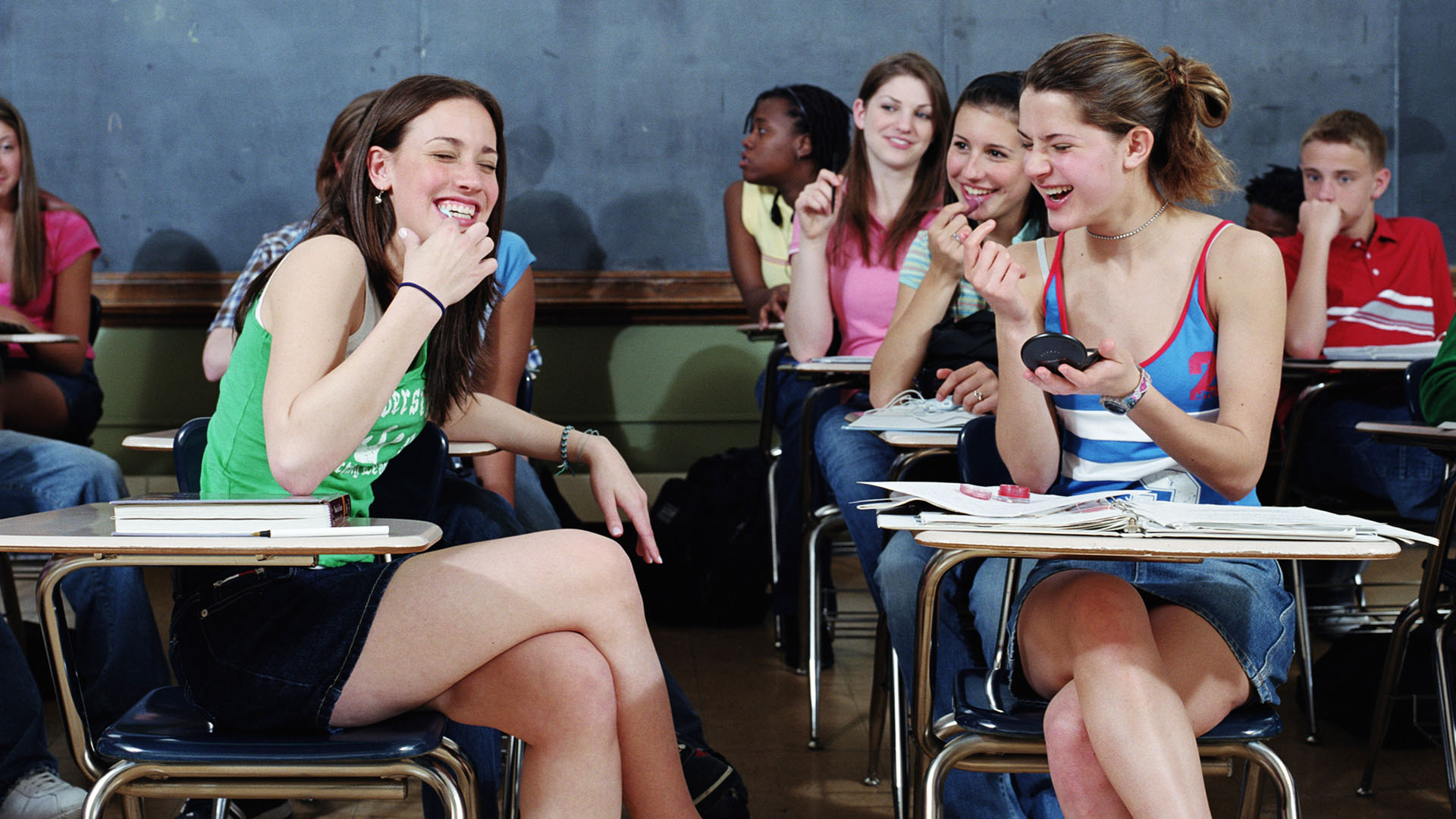 Teenagers (15-18) in classroom, girls laughing